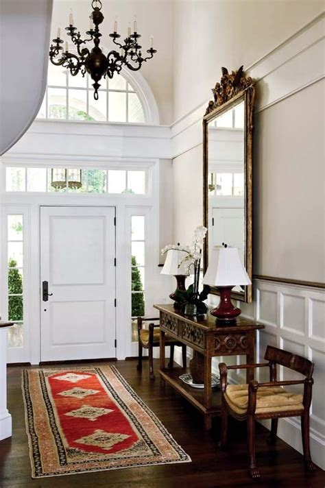 The high-ceiling foyer is outfitted with antiques